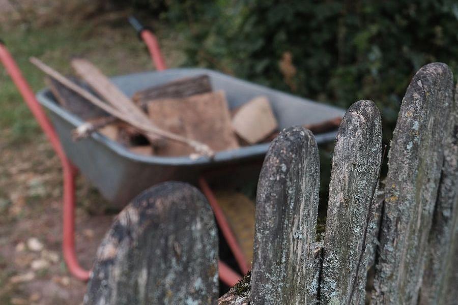 Schubkarre vor Zaun