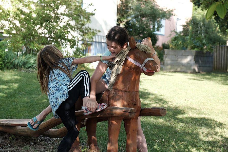 Zwei Mädchen auf einem Spielpferd