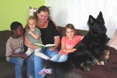 Frau mit drei Kindern und Hund auf dem Sofa