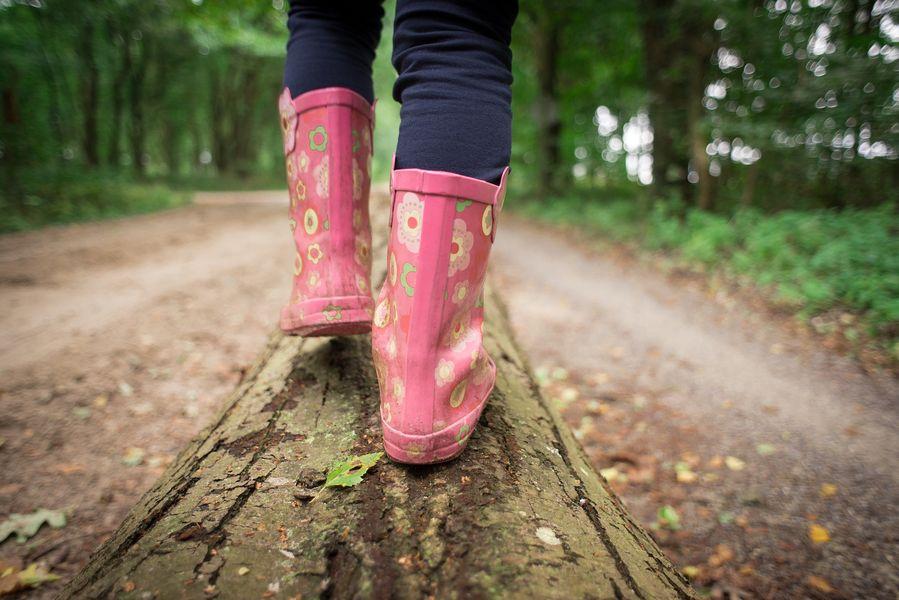 Füße mit Gummistiefeln balancieren auf Baumstamm