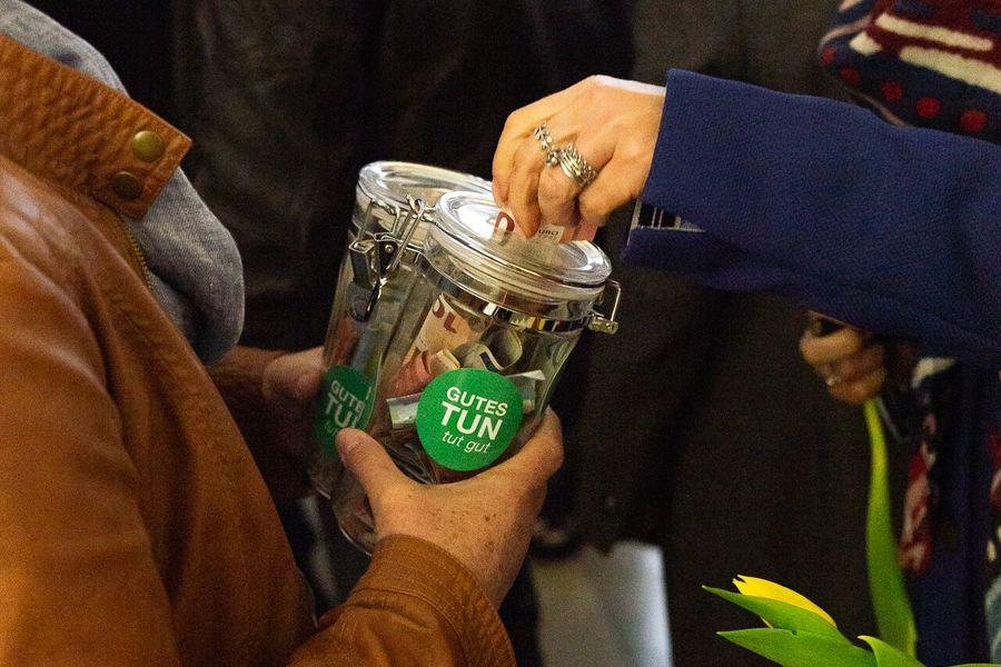 Hand steckt Geld in Spendendose